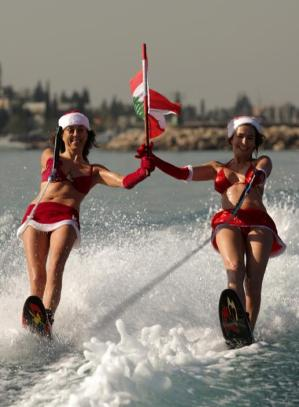Two Lebanese women wearing Santa Claus outfits and waving their national flag water ski during a show in the bay of Jounieh, 20 kms North of Beirut, on December 24, 2013. AFP PHOTO / PATRICK BAZ