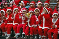 Students dressed as Santa Claus participate in Christmas celebrations at a school in Jammu, India, Wednesday, Dec. 24, 2014. Christians make up about 2 percent of the population in India, a secular country of more than 1 billion people where Hindus form the overwhelming majority. (AP Photo/Channi Anand) DEL112