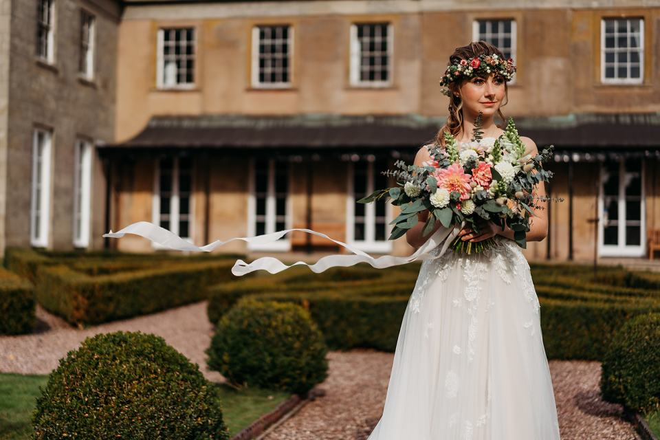 Fillongley hall warwickshire wedding venue - photo of bride in the formal gardens holding wedding bouquet with ribbons in the wind