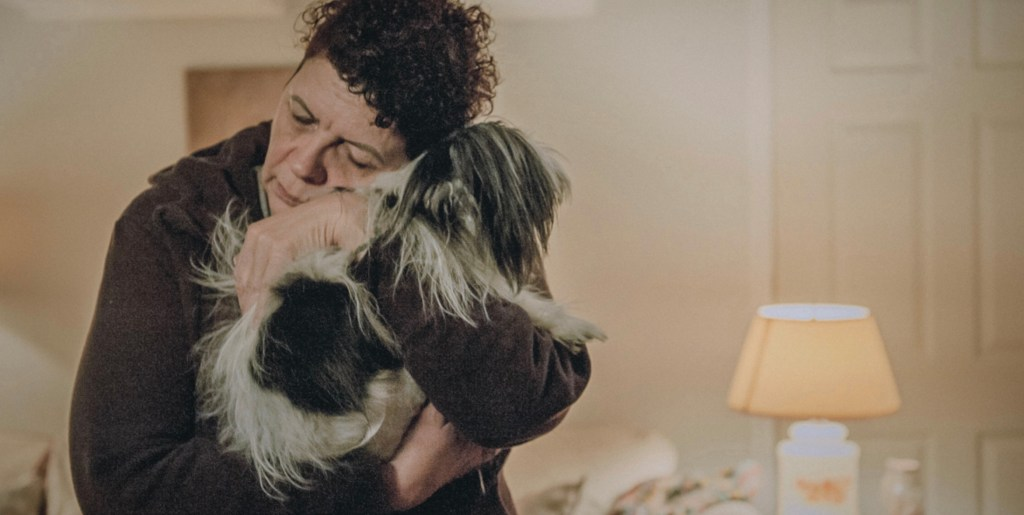 Image Description: A white room is in the background with a beige lamp. In the foreground is an old white woman with short curly brown hair and wearing a dark purple hoodie. She is cuddling a grey-and-white small dog.