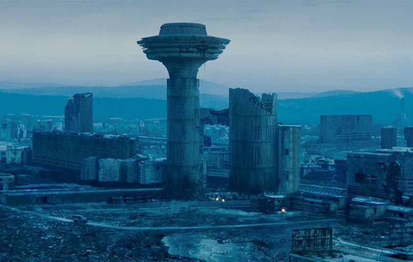 Image Description: The entire landscape is in ruins and is tinted a navy blue colour. There are hills in the distance, but in the foreground are some buildings. One of the buildings is a column that is destroyed at the top, whilst the other column is in place, extending out at the top.