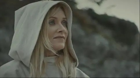 A woman, dressed in a white hooded robe, smiles slightly towards something off screen. In the background is an out of focus cliffside.