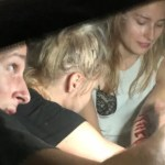 Three people are squeezed beside each other in a small car: the closest person is a man holding a light, in the middle is a woman applying special effects make up on the person on the far right, a woman with fake blood on her arm.