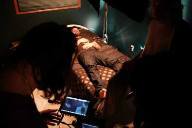 A still from the set of the short film Apparitions. The main actor laying in bed.
