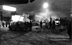 A black and white photo of a movie production outside in the desert.