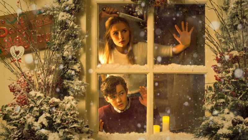 better watch out movie a woman and a man look out a window with a Christmas tree on the left hand side