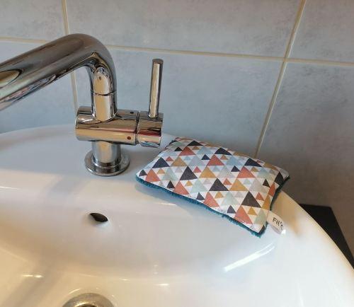 Eponge lavable au coin du lavabo triangles
