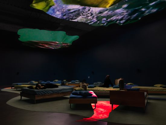 Pipilotti Rist, 4th Floor To Mildness, 2016. Video and sound installation with two projections onto two amorphous screens hanging horizontally from the ceiling, single and double beds with pillows and covers, four projectors, two moving mirrors, four media players, audio system, black sprinkler net, curtain, carpet, wall paint, neon, 8:11 min / 8:11 min / 7:03 min / 6:19 min. © Pipilotti Rist. Courtesy the artist, Hauser & Wirth, and Luhring Augustine. Music and text by Soap&Skin/Anja Plaschg. Courtesy Flora Musikverlag and [PIAS] Recordings. Installation photo: Maris Hutchinson / EPW Studio, courtesy New Museum.
