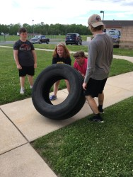 Two students tag team the tire flip as Hickman checks their form. (Photo/Jaryd Leady)