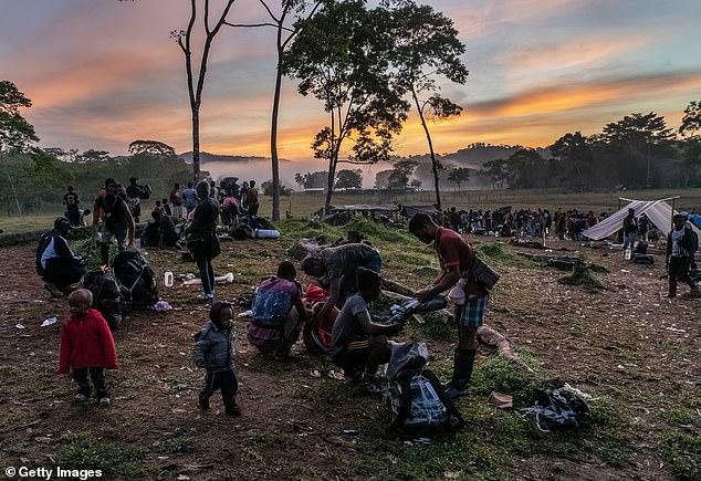 Mostly Haitian migrants break camp at sunrise on October 7 before trekking through the 66-mile stretch of undeveloped, unpoliced rainforest