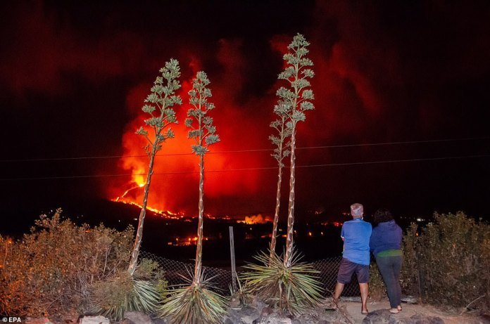 A couple look on as the Cumbre Vieja erupts in the early hours of Thursday morning, sending more lava creeping down its sides