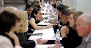 Job seekers have their resumes reviewed at a job fair expo in June in Anaheim, Calif. (AP file photo)
