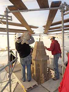 Workers install the top cap of one of the House of Hope pinnacles. The cap hides the topmost bolt attached to a tension rod holding the structure together. (Submitted photo)