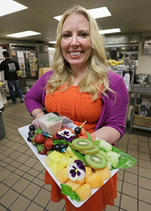 Kristen Wasyliszyn, owner of Atiki's Flight Catering, displays a fruit platter that is typical fare on a corporate jet.
