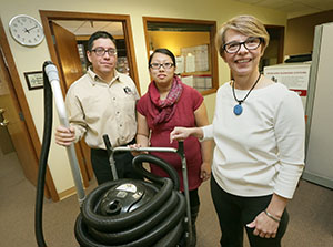 Cindy Banchy, right, stands in her Eagan office with a wet-dry vacuum, along with Mario Juarez and his fiancee, Mary Moua. The couple's Vanguard Cleaning Systems franchise initially covered the south and southwest metro, but now includes the east metro from Stillwater to St. Paul. (Staff photo: Bill Klotz)