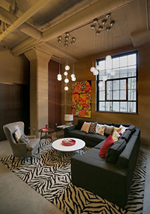 The first-floor lobby serves as a focal point of the Buzza Lofts and offers the same rugged industrial aesthetic seen in North Loop market-rate projects. (Staff photo: Bill Klotz)