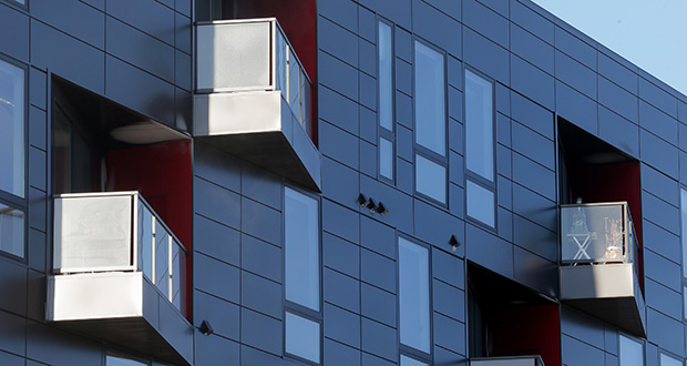 Clad in dark gray panels, the building's facade is broken up by exterior decks set at sharp angles, each highlighted by a red wall that adds a touch of color. (Staff photo: Bill Klotz)