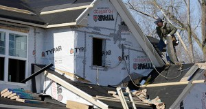 A builder works on the roof of a house under construction in Wilmette, Ill. (AP file photo)