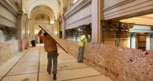 Workers on the third floor of the State Capitol put boards in place to protect walls and railings from damage during the building's renovation. Work is transitioning from the building's basement to the upper floors. (Staff Photo: Bill Klotz)
