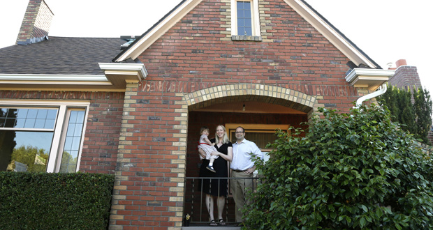Ryan Carson, right, stands with his wife, Jenny Roraback-Carson, and their daughter, Clara, 3, in the entry to their home in Seattle. The Carsons' mortgage rate is so low that it doesn't make financial sense to sell their home, even if they need more space. (AP photo)