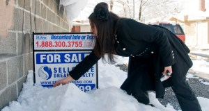 "Realtor Sarah Carmona of Sellstate Dreams Realty moves snow in front of a ""For Sale"" sign outside a foreclosed home in Reno, Nevada, in February 2010. While investors turned many distressed homes in Nevada and elsewhere into rentals, corporate owners with limited capital are now selling houses in bulk, or one by one."