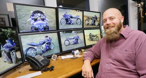 Josh Headlee, CEO and co-founder of St. Paul-based Accelerated Innovations, has eight computer monitors on his desk to keep track of business. But his screensaver features the custom motorcycle he owns. (Staff photo: Bill Klotz)