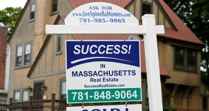 A sign hangs July 10 in front of a recently sold home in Quincy, Mass. (AP Photo)