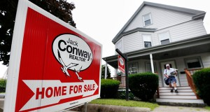 A postal carrier delivers mail to a house for sale in Quincy, Mass. (AP file photo)