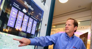Sam Rogers, CEO of AlivePromo, points out an interactive display in Gaviidae Common I that serves as a building directory, provides weather info and more. (Staff photo: Bill Klotz)