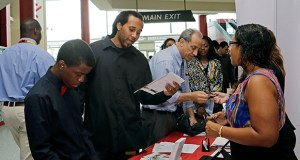 Job seeker Stephen Watson, of Fort Lauderdale, second from left, reviews the job qualifications during a job fair Aug. 19, 2014 in Sunrise, Florida. (AP photo: Alan Diaz)