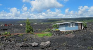 A house sits among recent lava flow Thursday in Kalapana, Hawaii. Ten miles from Pahoa, the small Hawaii town held hostage by a slowly oozing stream of lava from Kilauea volcano, people are rebuilding on land that was almost entirely swallowed by molten rock nearly 30 years ago. (AP Photo: Audrey McAvoy)