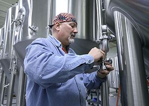 Steve Carlyle installs a valve on a fermentation tank at Badger Hill Brewing in Shakopee. Carlyle, who owns OC Mechanical Inc., hopes to build his own brewery and taproom in Robbinsdale. (Staff photo: Bill Klotz)