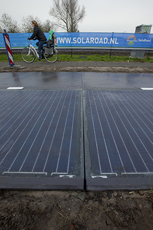 A woman and a child ride over the sidewalk Tuesday, passing a stretch of bicycle path where a solar panel roadway is being constructed in Krommenie, north of Amsterdam, Netherlands. (AP Photo: Peter Dejong)