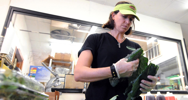 Christi Ferretti, co-owner and chef of Pine Valley Market, cuts kale Oct. 23 at the market in Wilmington, N.C. The Institute for Supply Management, a trade group of purchasing managers, said the pace of growth slowed for U.S. services firms in October. (AP Photo: The Star-News, Matt Born)