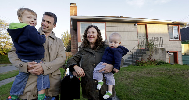 Jennifer Ewing, second right, and her husband Florian Thiel pose for photos Oct. 15 with their children Max, left, 3, and Felix, 8-months, outside their new home in Seattle's Ballard neighborhood. The couple recently closed on the three-bedroom house, which cost slightly less than $500,000. They moved to Seattle from New York, another city that matches the pattern of high-income jobs and even more expensive housing. AP Photo: Elaine Thompson