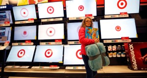 A customer walks past a bank of flat screen televisions Nov. 28 at a Target store in South Portland, Maine. Target Corp. reported a loss in its fourth quarter on Wednesday but said it recorded stronger-than-expected sales during the holiday season. (AP File photo)