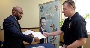 U.S. Marine Corps Veteran Arlington Robertson, of Fort Lauderdale, left, hands his resume to an Internal Revenue Service Special Agent, at the annual Veterans Career and Resource Fair on Feb. 6 in Miami. The Labor Department reported Friday that the unemployment rate fell to 5.5 percent. (AP Photo: Alan Diaz)