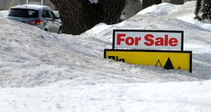 """A """"for sale"""" sign pokes out of about 4 feet of snow Feb. 24 in the front yard of a home listed in Derry, N.H. The National Association of Realtors reported Monday thatsales of existing homes rose 1.2 percent in February. (AP File Photo)"""