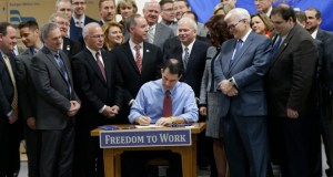Wisconsin Gov. Scott Walker signs a right-to-work bill into law Monday, March 9, 2015 at Badger Meter in Brown Deer, Wis. The new law, which takes effect immediately, makes Wisconsin the 25th right-to-work state and the first to do it since Michigan and Indiana in 2012. (AP Photo/Milwaukee Journal-Sentinel, Mike De Sisti)