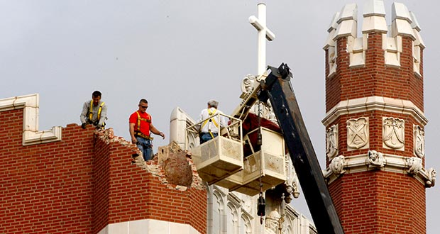 Maintenance workers inspect the damage to one of the spires on Benedictine Hall Nov. 6, 2011, at St. Gregory's University following a magnitude-5.0 earthquake in Shawnee, Okla. A government report released Thursday found that a dozen areas in the United States have been shaken in recent years by small earthquakes triggered by oil and gas drilling. (AP File Photo)