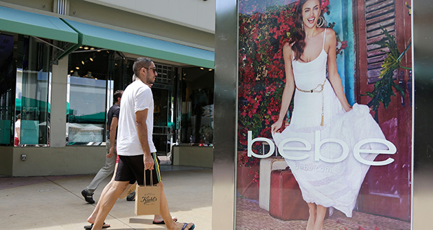 "Shoppers walk past an advertisement for retailer ""bebe"" on March 13 along Lincoln Road Mall, a pedestrian street featuring retail stores and outdoor cafes, in Miami Beach, Fla. The University of Michigan reported Friday that its index of consumer sentiment dropped in May. (AP file photo)"
