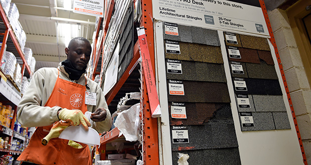Prince Addy of Manassas, Va., straightens up the shelves of roofing products Feb. 23 at the Home Depot in Falls Church, Va. Home Depot reported Tuesday that sales at its U.S. stores open at least a year were up 7.1 percent in the first quarter. (AP file photo)