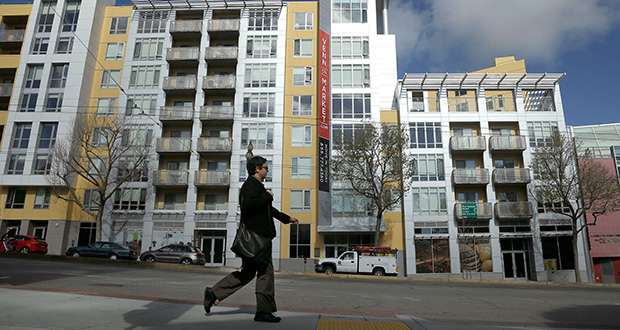 The biggest increase in the Standard & Poor's/Case-Shiller 20-city home price index was in San Francisco, where prices rose 10.3 percent. In this March 2014 photo, a woman walks across the street from the Venn on Market apartment and condominium building in San Francisco. (AP file photo)