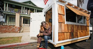 "Irene ""Smokie"" McGhee, a woman who had been sleeping on the streets in a South Los Angeles neighborhood, listens to music Thursday in the doorway of her newly built tiny home in Los Angeles. (AP Photo: Damian Dovarganes)"