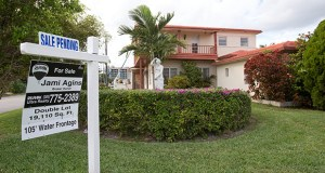 """A """"sale pending"""" sign is posted atop a realty sign Jan. 8 in front of a home in Surfside, Fla. The National Association of Realtors said Thursday that its pending home sales index climbed for the fourth consecutive month. (AP file photo)"""