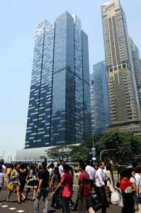 Pedestrians cross a road in June 2013 in front of the Asia Square towers, left, which houses the offices of Citigroup Inc. BlackRock said it has received expressions of interest for Singapore's Asia Square Tower 1 and may also look to sell Asia Square Tower 2. (Bloomberg file photo)