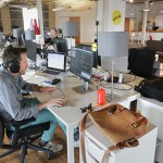 BuzzFeed's 23 employees work at laptops on long tables, doing full-stack app development for Android and IOS.