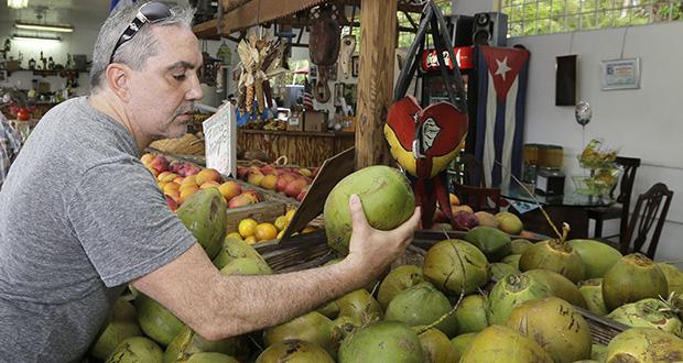 Shopper Julian Fojon-Losada, of Georgia, checks a coconut June 9 at a local fruit store in the Little Havana area of Miami. The Commerce Department reported Thursday that consumer spending rose 0.9 percent last month. (AP Photo: Alan Diaz)