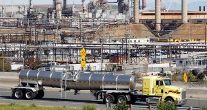 A tanker truck passes the Chevron oil refinery in March 2010 in Richmond, California. The Federal Reserve said Monday that a decline in refining oil caused U.S. factory output to slip in May 2015, overshadowing solid gains by automakers. (AP File Photo)