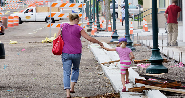 Two pedestrians navigate the 1000 block of Mainstreet in Hopkins. The road is under construction and several initiatives are planned to help businesses.  (Staff photo: Bill Klotz)